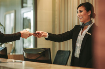 Smiling receptionist behind the hotel counter attending female guest. Concierge giving the documents to hotel guest.