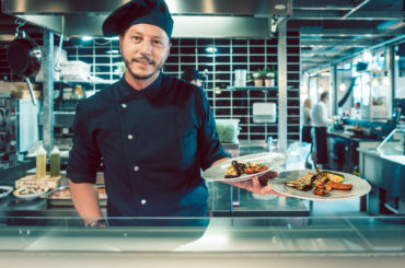 Portrait of a confident and experienced master chef holding two plates with tasty grilled vegetables behind the counter of a trendy restaurant